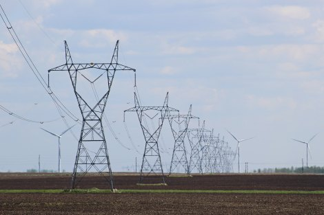 Transmission towers and wind turbines on the field.